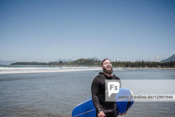 Mann mit Surfbrett am Strand  Tofino  Kanada