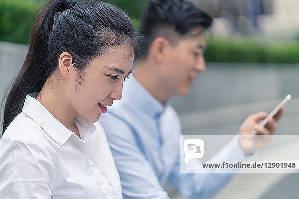 Junge Geschäftsfrau und junger Mann schauen auf Smartphone in der Stadt  Shanghai  China