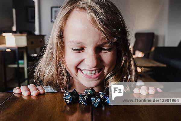 Lächelndes Mädchen am Tisch betrachtet Rollenspielwürfel  Nahaufnahme