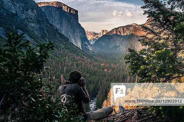 Rock climber taking photograph of mountain ranges  Yosemite National Park  California  USA