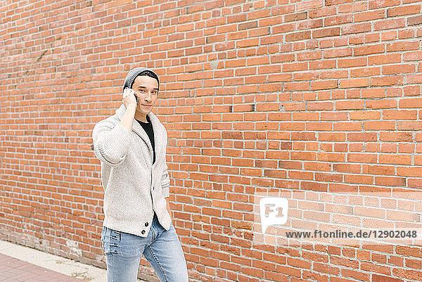 Junger Mann telefoniert  während er an einer Ziegelmauer entlanggeht  Vancouver  Kanada