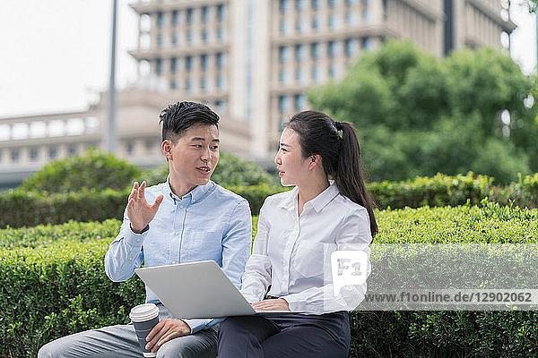 Junge Geschäftsfrau und junger Mann benutzen Laptop und plaudern am Sitz der Stadt  Shanghai  China