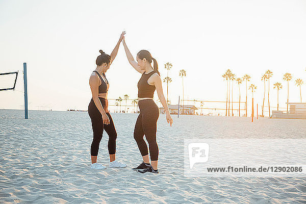 Friends hi fiving on beach  Long Beach  California  US