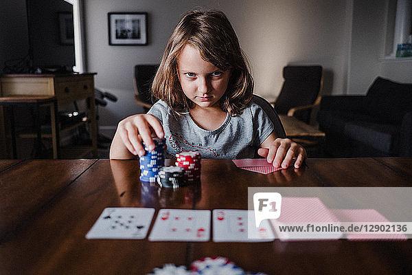 Mädchen mit einem Stapel Spielchips  die am Tisch Karten spielt  Portrait
