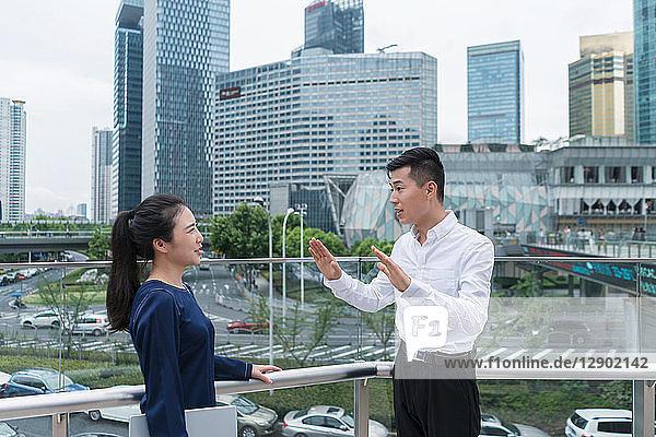 Junge Geschäftsfrau und Mann unterhalten sich auf dem Balkon im Finanzbezirk der Stadt  Shanghai  China