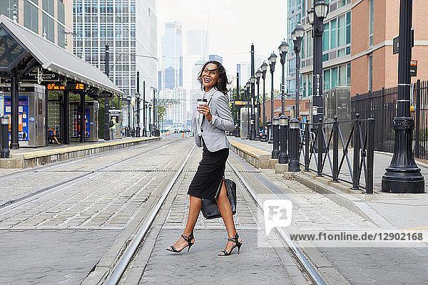 Geschäftsfrau überquert Stadtbahnschienen