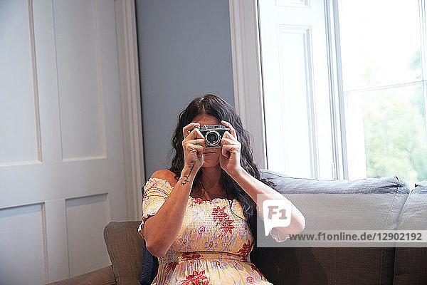 Woman using camera on sofa
