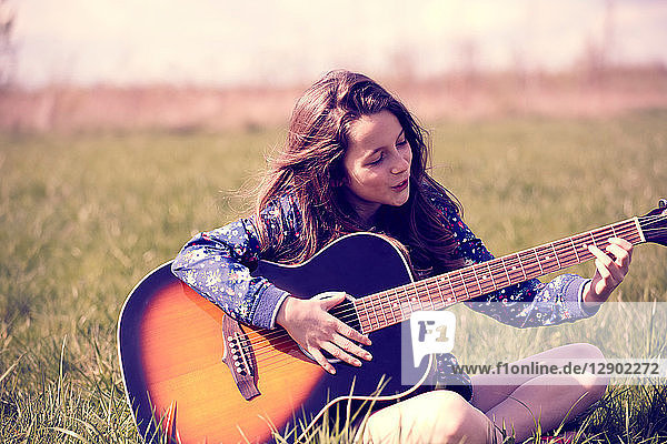 Girl playing guitar on grass
