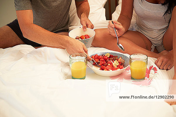 Couple sharing fruit and orange juice breakfast in bed  cropped