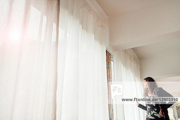 Woman peering out through net curtained window