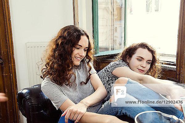 Zwei junge Freundinnen sitzen auf einem Sessel