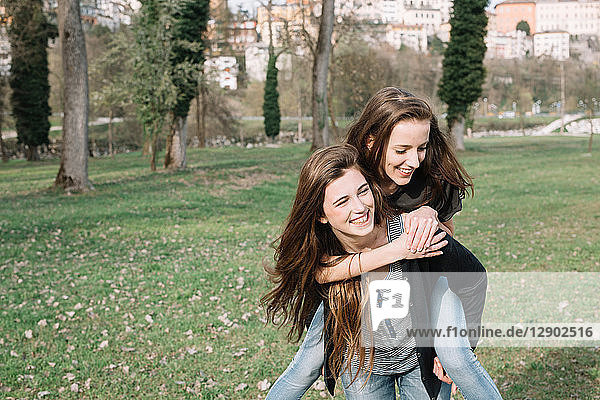 Girlfriends playing piggyback ride in park