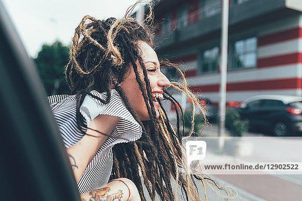 Frau lehnt sich aus dem Autofenster