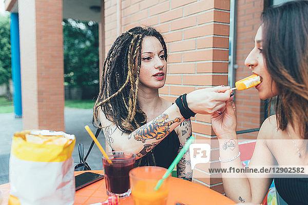 Freundinnen teilen sich Eis im Café