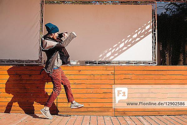 Hipster tanzen auf einer Holzterrasse neben der Bühne