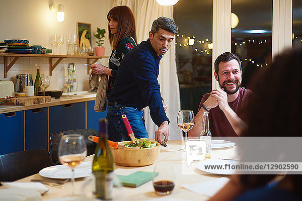 Friends talking  man setting table at dinner party