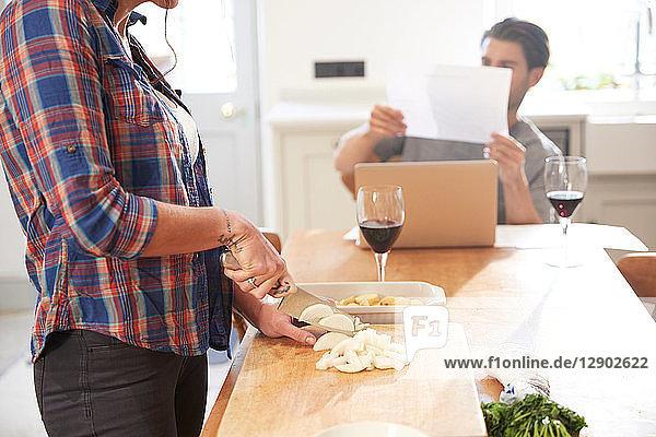 Woman preparing vegetables at kitchen table  boyfriend reading paperwork