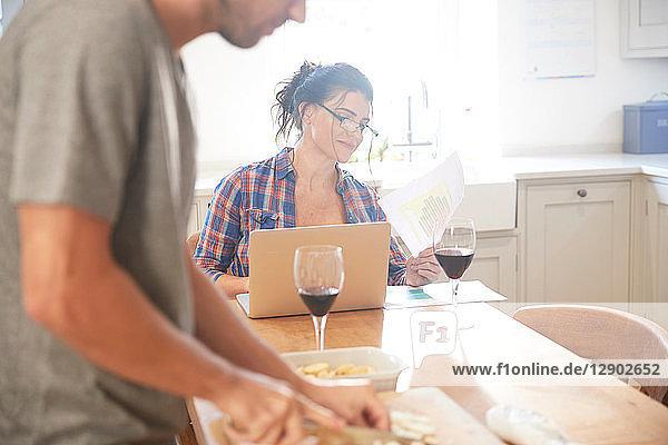 Man preparing vegetables at kitchen table  girlfriend reading paperwork