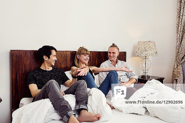 Young woman and male friends sitting chatting on bed