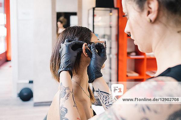 Tätowierer sticht einem Kunden im Salon das Ohr