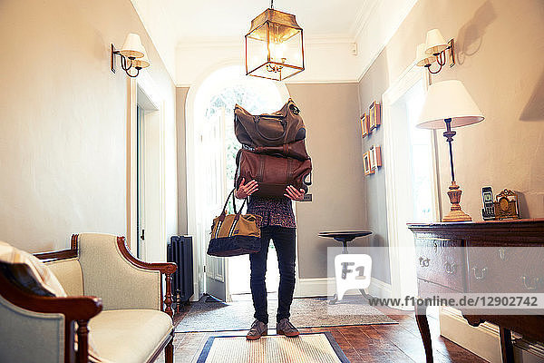 Young man carrying stack of luggage in hotel lobby