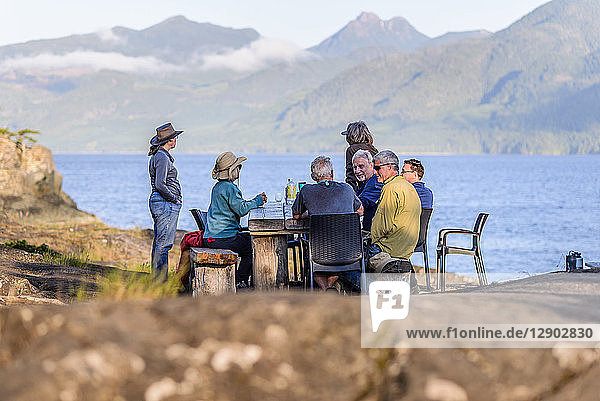 Friends talking at dinner on lakeside,  Johnstone Strait,  Telegraph Cove,  Canada