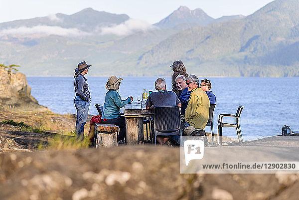 Freunde sprechen beim Abendessen am Seeufer  Johnstone Strait  Telegraph Cove  Kanada