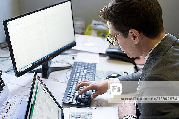 Mann benutzt Laptop und Desktop im Büro