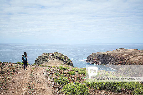 Woman hiking on coastal dirt track  Las Palmas  Gran Canaria  Canary Islands  Spain