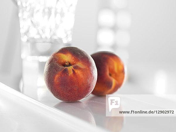 Pfirsiche auf glänzend weißer Oberfläche