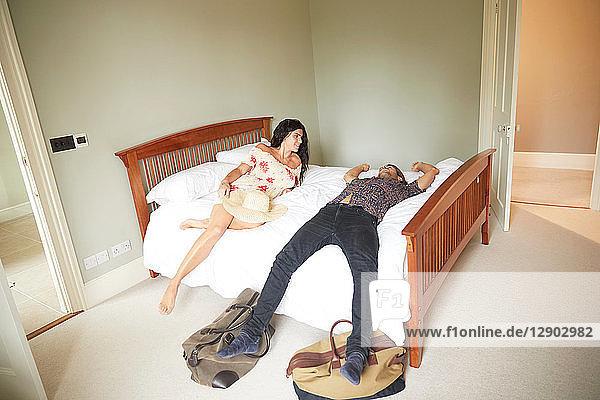 Couple lying on hotel bed