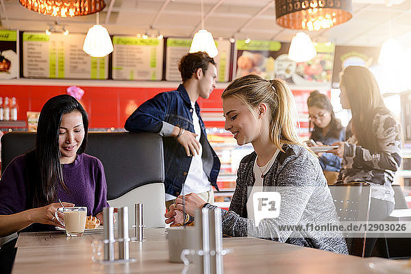 Mid adult woman and friend having coffee in cafe
