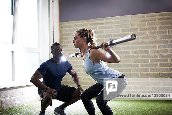 Trainer watching female client do squats with barbell in gym