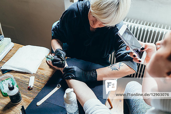 Woman tattooing friend's arm at home