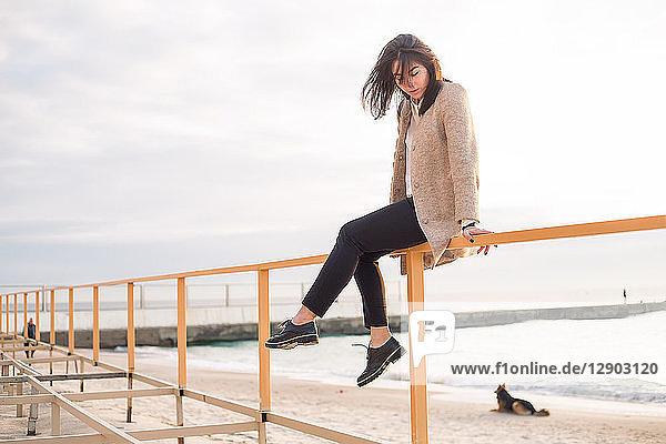 Frau sitzt am Strand am Geländer