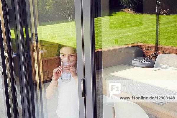 Junges Mädchen trinkt Wasser an der Terrassentür