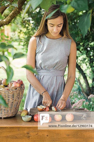 Frau schneidet Äpfel auf dem Tisch