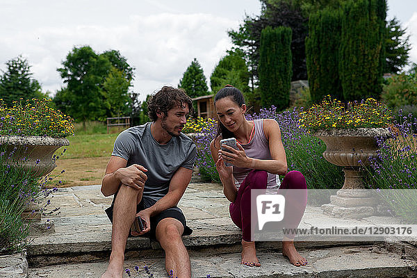 Man and woman practicing yoga in garden  looking at smartphones on patio