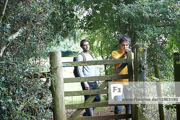 Hiker couple opening farm gate