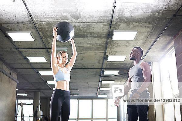 Trainer beobachtet weiblichen Klienten beim Heben eines Medizinballs im Fitnessstudio