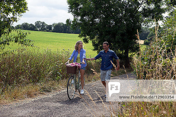 Mature couple strolling and cycling on rural road