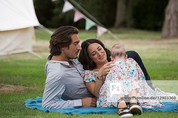 Ehemann und Ehefrau mit Baby im Garten Ehemann und Ehefrau mit Baby im Garten
