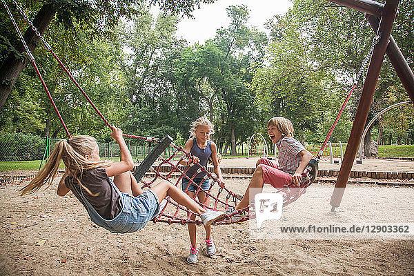 Kinder spielen auf der Netzschaukel