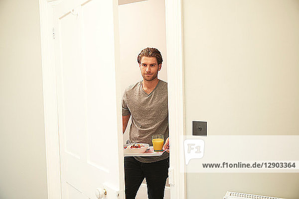 Young man carrying breakfast tray into bedroom