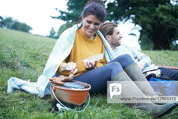 Couple sitting in rural field cooking on barbecue grill