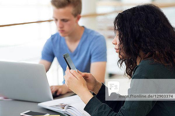 Highschool-Mädchen am Klassenzimmer-Schreibtisch mit Blick auf Smartphone