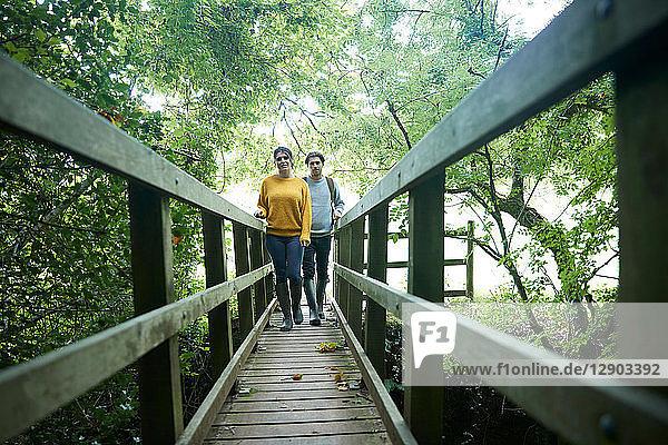 Hiker couple crossing wooden bridge