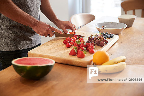 Young man slicing fresh fruit at kitchen table  mid section