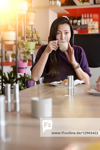 Mid adult woman drinking coffee in cafe