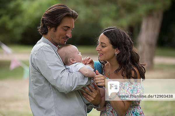 Ehemann und Ehefrau mit Baby im Garten
